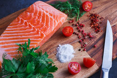 Fresh raw salmon fillet with spices. Raw salmon fillet and ingredients for cooking on a wooden cutting board Stock Photos