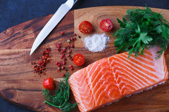 Fresh raw salmon fillet with spices. Raw salmon fillet and ingredients for cooking on a wooden cutting board Royalty Free Stock Image