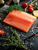 Fresh raw salmon fillet steak with aromatic herbs, spices.  Stock Photo
