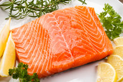 Fresh raw salmon fillet. On white plate Royalty Free Stock Photos