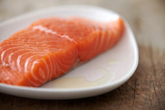 Fresh raw salmon fillet. On white plate, selective focus Stock Images