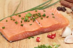 Fresh raw salmon fillet on wood background. Royalty Free Stock Images