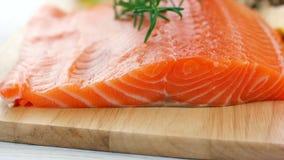 Fresh raw salmon fillet on wooden board stock footage