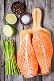 Fresh raw salmon fillet on a wooden cutting board with asparagus. Top view Royalty Free Stock Images