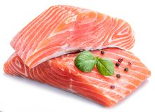 Fresh raw salmon fillets decorated with fresh basil. Fresh raw salmon fillets decorated with fresh basil on white background Stock Image