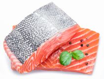Fresh raw salmon fillets decorated with green basil. Fresh raw salmon fillets decorated with green basil on white background Royalty Free Stock Photos