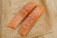 Fresh raw salmon fillets. Two fresh uncooked salmon fillets with seasoning on greaseproof paper Royalty Free Stock Photo