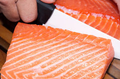 Fresh raw salmon fish. On wooden board cutting by the cook using a white knife Stock Image
