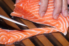 Fresh raw salmon fish. On wooden board cutting by the cook using a white knife Royalty Free Stock Image