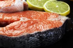 Fresh raw salmon fish steaks with fresh herbs on stone backgroun Royalty Free Stock Photo