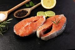 Fresh raw salmon fish steaks with fresh herbs on stone backgroun Stock Photography