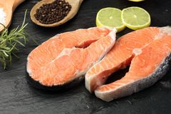 Fresh raw salmon fish steaks with fresh herbs on stone backgroun Royalty Free Stock Photos