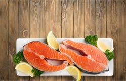 Fresh raw salmon with salt and lemon on wooden. Fresh raw salmon green red closeup market Stock Photo