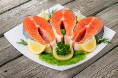 Fresh raw salmon on white plate. Fresh raw salmon green red closeup market Stock Image