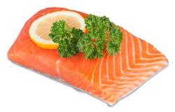 Fresh raw salmon with salt and lemon on white. Fresh raw salmon green red closeup market Royalty Free Stock Image