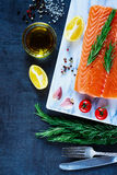 Fresh raw salmon. Healthy food - raw salmon fillet, preparation with fresh seasoning, olive oil and lemon on marbre cutting board. Background layout with free Royalty Free Stock Photo