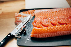 Fresh raw salmon in kitchen. Fresh raw salmon - removing skin for elegant dinner preparation Stock Photo