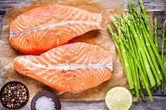 Fresh raw salmon medallions with asparagus and lime top view. Fresh raw salmon medallions with asparagus and lime on the wooden table Royalty Free Stock Photo