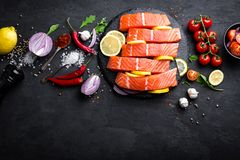 Fresh raw salmon red fish fillet on black background. Top view Stock Image