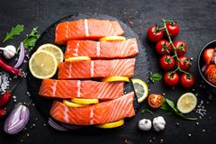 Fresh raw salmon red fish fillet on black background. Top view Stock Photography