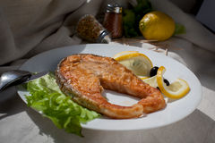Fresh Raw Salmon Red Fish Steak. Grilled fish steak with lemon and salad Royalty Free Stock Image