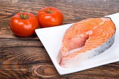Fresh raw salmon red fish steak with herbs and vegetables Royalty Free Stock Photo