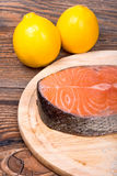Fresh raw salmon red fish steak with herbs and vegetables Royalty Free Stock Images
