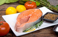 Fresh raw salmon red fish steak with herbs and vegetables. Fresh raw salmon red fish steak with herbs, spices and vegetables Stock Images