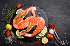 Fresh raw salmon red fish steaks on black background. Top view Stock Photos