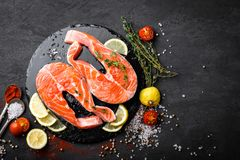 Fresh raw salmon red fish steaks on black background. Top view Stock Photo