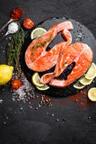 Fresh raw salmon red fish steaks on black background. Top view Royalty Free Stock Photos