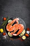 Fresh raw salmon red fish steaks on black background. Top view Stock Images