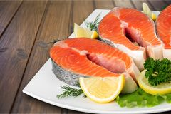 Fresh raw salmon with salt and lemon on wooden. Fresh raw salmon green red closeup market Royalty Free Stock Photography