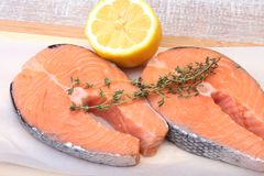 Fresh raw salmon with spices and lemon on wooden cutting board. ready for cookin Stock Photography