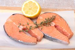 Fresh raw salmon with spices and lemon on wooden cutting board. ready for cookin.  Royalty Free Stock Image