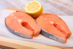 Fresh raw salmon with spices and lemon on wooden cutting board. ready for cookin.  Stock Image