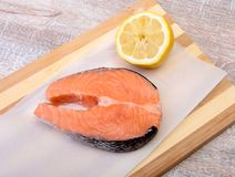 Fresh raw salmon with spices and lemon on wooden cutting board. ready for cookin.  Stock Photo