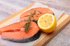Fresh raw salmon with spices and lemon on wooden cutting board. ready for cookin.  Royalty Free Stock Photo