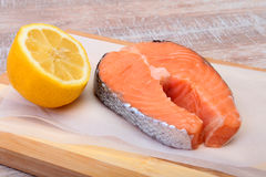 Fresh raw salmon with spices and lemon on wooden cutting board. ready for cookin Royalty Free Stock Image