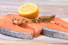 Fresh raw salmon with spices and lemon on wooden cutting board. ready for cookin Royalty Free Stock Photography