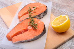 Fresh raw salmon with spices and lemon on wooden cutting board. ready for cookin Royalty Free Stock Photos