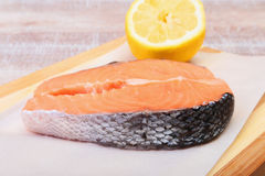 Fresh raw salmon with spices and lemon on wooden cutting board. ready for cookin Stock Photos