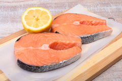 Fresh raw salmon with spices and lemon on wooden cutting board. ready for cookin.  Stock Photography