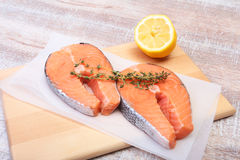 Fresh raw salmon with spices and lemon on wooden cutting board. ready for cookin.  Royalty Free Stock Images