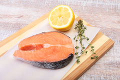 Fresh raw salmon with spices and lemon on wooden cutting board. ready for cookin Stock Image