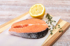 Fresh raw salmon with spices and lemon on wooden cutting board. ready for cookin Royalty Free Stock Photo