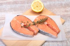 Fresh raw salmon with spices and lemon on wooden cutting board. ready for cookin.  Royalty Free Stock Photography