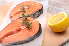Fresh raw salmon with spices and lemon on wooden cutting board. ready for cookin Stock Images
