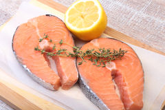 Fresh raw salmon with spices and lemon on wooden cutting board. ready for cookin.  Royalty Free Stock Photos