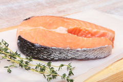 Fresh raw salmon with spices on wooden cutting board. ready for cookin Royalty Free Stock Images